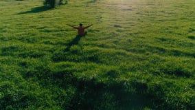 Ακτινωτή πτήση χαμηλού υψομέτρου πέρα από το άτομο αθλητικής γιόγκας στην τέλεια πράσινη χλόη Ηλιοβασίλεμα στο βουνό απόθεμα βίντεο