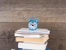 Ακόμα ζωή γύρω από το ρολόι στο σωρό των βιβλίων Έννοια εκπαίδευσης και εκμάθησης Επενδύστε το χρόνο στις μελέτες Χρόνος να αναβα Στοκ Φωτογραφία