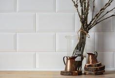 Ακόμα-ζωή εσωτερική κουζίνα χαλκός που μετρά τα φλυτζάνια στους ξύλινους κύκλους με τους κλάδους ιτιών σε έναν ξύλινο πίνακα Στοκ Φωτογραφίες