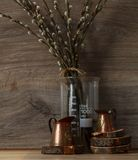 Ακόμα-ζωή εσωτερική κουζίνα χαλκός που μετρά τα φλυτζάνια στους ξύλινους κύκλους με τους κλάδους ιτιών σε έναν ξύλινο πίνακα Στοκ εικόνα με δικαίωμα ελεύθερης χρήσης