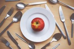 Ακόμα ζωή: Η κόκκινη Apple που βρίσκεται στο μικρό πιάτο Κουτάλια, κουτάλια τσαγιού, δίκρανα και μαχαίρια στο ξύλινο γραφείο ως υ Στοκ εικόνες με δικαίωμα ελεύθερης χρήσης