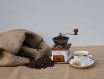 Ακόμα ζωή με έναν νοσταλγικό μύλο καφέ και ένα φλυτζάνι καφέ με τον πρόσφατα γίνοντα καφέ στοκ φωτογραφία με δικαίωμα ελεύθερης χρήσης