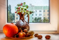 Ακόμα ζωή με μια κολοκύθα και μια στάμνα στο παράθυρο Στοκ Εικόνες