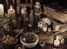 Ακόμα ζωή με τα βιβλία μαγισσών, τους κυλίνδρους, τα χορτάρια και τα μαγικά αντικείμενα στοκ εικόνα