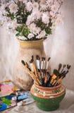 Ακόμα ζωή με τα λουλούδια και τις βούρτσες σε ένα παλαιό δοχείο Στοκ φωτογραφία με δικαίωμα ελεύθερης χρήσης
