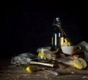 Ακόμα ζωή με τα μήλα, το χυμό μήλων, τα παλαιά βιβλία και ένα ασημένιο μαχαίρι σε έναν ξύλινο πίνακα σε ένα σκοτεινό υπόβαθρο Τρύ Στοκ Εικόνες