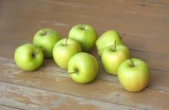 Ακόμα ζωή με τα πράσινα μήλα στην καφετιά κινηματογράφηση σε πρώτο πλάνο υποβάθρου ξυλείας Στοκ Εικόνα