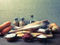 Ακόμα ζωή με τα ψάρια, τα λαχανικά και τα καρυκεύματα σε έναν ξύλινο πίνακα Τ Στοκ Φωτογραφία