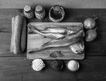 Ακόμα ζωή με τα ψάρια, τα λαχανικά και τα καρυκεύματα σε ένα ξύλινο backgrou Στοκ Εικόνες
