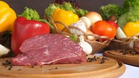 Ακόμα ζωή με το ακατέργαστο κρέας χοιρινού κρέατος και τα φρέσκα λαχανικά φιλμ μικρού μήκους