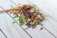 Ακόμα ζωή με το γλυκό ρύζι με το λούστρο ζάχαρης και την καραμέλα σοκολάτας στο ξύλινο υπόβαθρο Στοκ Φωτογραφίες