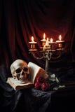 Ακόμα ζωή με το κρανίο, το βιβλίο και το κηροπήγιο Στοκ Φωτογραφία