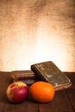 Ακόμα ζωή με το μήλο, το πορτοκάλι και έναν σωρό των παλαιών βιβλίων στο παλαιό wo Στοκ Εικόνες