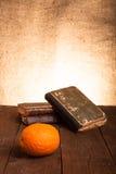Ακόμα ζωή με το πορτοκάλι και έναν σωρό των παλαιών βιβλίων στο παλαιό ξύλινο TA Στοκ Εικόνα