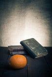 Ακόμα ζωή με το πορτοκάλι και έναν σωρό των παλαιών βιβλίων στο παλαιό ξύλινο TA Στοκ φωτογραφία με δικαίωμα ελεύθερης χρήσης