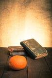 Ακόμα ζωή με το πορτοκάλι και έναν σωρό των παλαιών βιβλίων στο παλαιό ξύλινο TA Στοκ Εικόνες