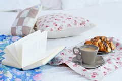 Ακόμα ζωή με το πρόγευμα και ένα βιβλίο στο κρεβάτι Στοκ εικόνα με δικαίωμα ελεύθερης χρήσης
