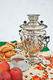Ακόμα ζωή με το ρωσικούς παραδοσιακούς σαμοβάρι, το κύπελλο και τους ρόλους Στοκ Εικόνες