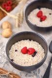 Ακόμα ζωή με oatmeal και τα φρέσκα σμέουρα στα καθαρισμένα κύπελλα Στοκ Εικόνα