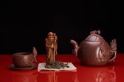 Ακόμα ζωή με statuette το πνεύμα τσαγιού, πράσινο τσάι, πιατικά Στοκ φωτογραφίες με δικαίωμα ελεύθερης χρήσης