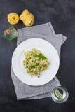 Ακόμα ζωή - σπιτικά ζυμαρικά από το βασιλικό και arugula με το πράσινο pesto σε ένα άσπρο πιάτο σε ένα σκοτεινό υπόβαθρο Στοκ εικόνα με δικαίωμα ελεύθερης χρήσης