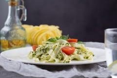Ακόμα ζωή - σπιτικά ζυμαρικά από το βασιλικό και arugula με το πράσινο pesto σε ένα άσπρο πιάτο σε ένα σκοτεινό υπόβαθρο Στοκ Φωτογραφίες