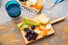 Ακόμα ζωή του τυριού, φρούτα, κρασί σε μια φυσική μαρμάρινη επιφάνεια Στοκ Φωτογραφίες