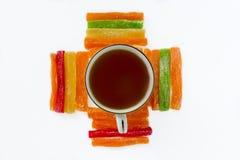 Ακόμα ζωή - το μαύρο τσάι σε ένα φλυτζάνι, γύρω από την είναι ευθυγραμμισμένο πολύχρωμο Στοκ φωτογραφίες με δικαίωμα ελεύθερης χρήσης