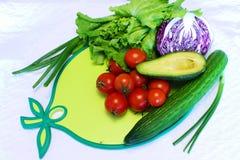 Ακόμα ζωή των λαχανικών και των πρασίνων σε έναν τέμνοντα πίνακα Στοκ Εικόνες