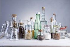 Ακόμα ζωή των διαφανών μπουκαλιών, των δοχείων και των γυαλιών γυαλιού Στοκ Εικόνες