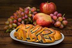 Ακόμα ζωή των σπιτικών ζυμών, γλυκιά πίτα παπαρουνών στο υπόβαθρο των νωπών καρπών, των μήλων και των σταφυλιών Στοκ Φωτογραφίες