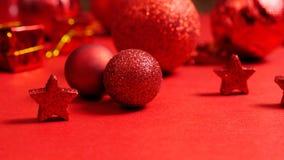 Ακόμα ζωή των σύγχρονων κόκκινων διακοσμήσεων Χριστουγέννων που στέκονται σε έναν κόκκινο πίνακα Στοκ φωτογραφίες με δικαίωμα ελεύθερης χρήσης