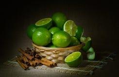Ακόμα ζωή, φρούτα ασβέστη σε ένα ψάθινο καλάθι, κανέλα, σκοτεινό υπόβαθρο στοκ φωτογραφίες με δικαίωμα ελεύθερης χρήσης