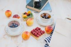Ακόμα η ζωή με δύο φλυτζάνια του τσαγιού σε έναν τρύγο κοιλαίνει και δύο tarts με τους νωπούς καρπούς σε ένα άσπρο εκλεκτής ποιότ Στοκ Φωτογραφία