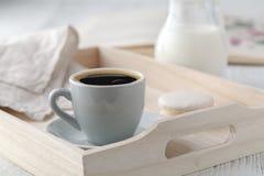 Ακόμα λεπτομέρειες ζωής, φλυτζάνι του τσαγιού στον αναδρομικό εκλεκτής ποιότητας ξύλινο δίσκο σε ένα τραπεζάκι σαλονιού στο καθισ Στοκ Εικόνες