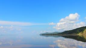 Ακόμα νερό και καθαρές αφές ουρανού στον ορίζοντα Ήρεμος ποταμός στο καλύτερο στοκ εικόνες