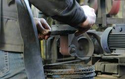 Αλέθοντας καταλύματα του μαχαιριού μετάλλων σε μια ζώνη-αλέθοντας μηχανή Κινηματογράφηση σε πρώτο πλάνο το των χεριών ατόμων ` s Στοκ Φωτογραφία