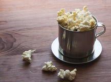 Αλατισμένο popcorn σε έναν ξύλινο πίνακα σε ένα κύπελλο μετάλλων Στοκ φωτογραφίες με δικαίωμα ελεύθερης χρήσης