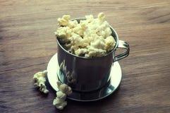 Αλατισμένο popcorn σε έναν ξύλινο πίνακα σε ένα κύπελλο μετάλλων Στοκ εικόνα με δικαίωμα ελεύθερης χρήσης