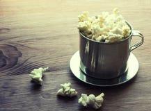 Αλατισμένο popcorn σε έναν ξύλινο πίνακα σε ένα κύπελλο μετάλλων Στοκ Εικόνα