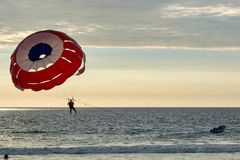 Αλεξίπτωτο που ωθείται με το ταχύπλοο στη θάλασσα με τις διακοπές ηλιοβασιλέματος στοκ εικόνες