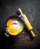 Αλεύρι με τα αυγά σε ένα τηγάνι με μια κυλώντας καρφίτσα και ένα σιτάρι στοκ εικόνα με δικαίωμα ελεύθερης χρήσης