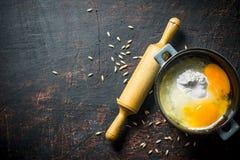 Αλεύρι με τα αυγά σε ένα τηγάνι με μια κυλώντας καρφίτσα και ένα σιτάρι στοκ εικόνες