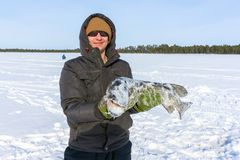 Αλιεία εκμετάλλευσης νεαρών άνδρων μια μεγάλη αλιεία πάγου λούτσων στοκ εικόνες