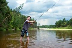 Αλιεία πριν από τη θύελλα Ένας νεαρός άνδρας πιάνει ένα ψάρι στην περιστροφή στοκ εικόνες