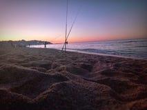 Αλιεία στην παραλία στο ηλιοβασίλεμα Στοκ φωτογραφία με δικαίωμα ελεύθερης χρήσης