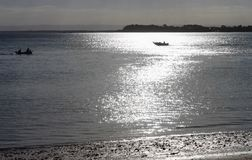 Αλιεία στο σούρουπο - δύο βάρκες που ταξιδεύουν στις αντίθετες κατευθύνσεις με την ελαφριά ανατροπή bokeh πέρα από το νερό από το στοκ φωτογραφία με δικαίωμα ελεύθερης χρήσης