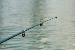 Αλιεία της κινηματογράφησης σε πρώτο πλάνο ράβδων επάνω από τη λίμνη με το μουτζουρωμένο υπόβαθρο νερού στοκ εικόνα με δικαίωμα ελεύθερης χρήσης