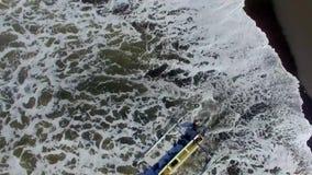 Αλιευτικά σκάφη που συντρίβονται από τα κύματα θάλασσας που οδήγησαν στην παραλία απόθεμα βίντεο