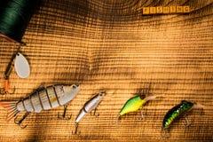 Αλιευτικό εργαλείο, τεχνητό δόλωμα σε ένα αρπακτικό ζώο σε ένα ξύλινο υπόβαθρο, τοπ άποψη με τα wobblers αλιείας επιγραφής και Στοκ Φωτογραφία
